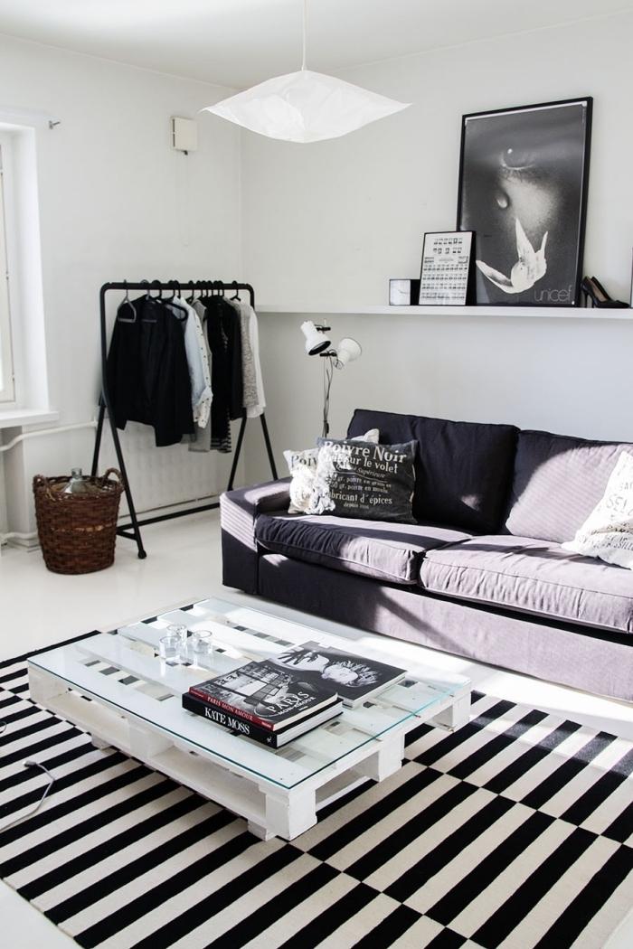 un salon scandinave monochrome avec une table basse en palette avec plateau en verre pour un rendu design