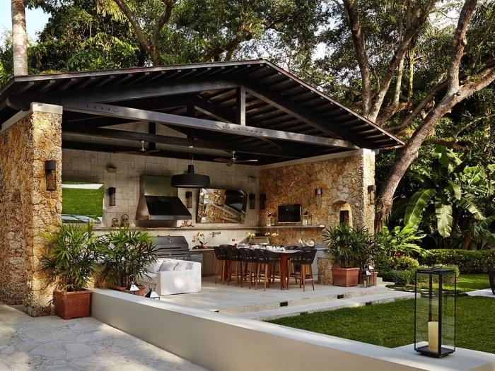 idée pour cuisine d été couverte avec toit de bois solide et mur en pierre, aménagement jardin avec table à manger