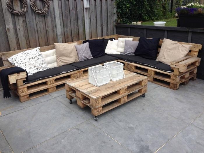coin extérieur au sol béton gris et murs de bois foncé avec mobilier en bois canapé d'angle et table basse en palette