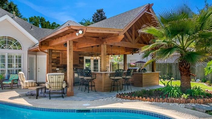 modèle de cuisine d'été couverte avec toit de bois et revêtement mural en bois foncé, ameublement extérieur avec chaises en fer forgé