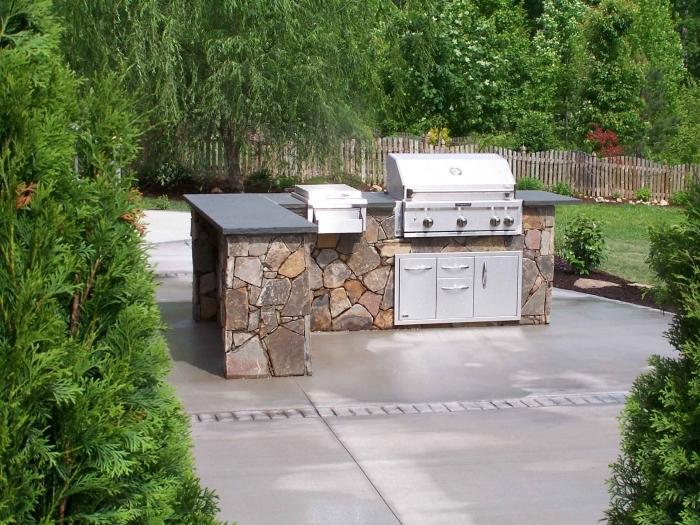 exemple de cuisine ouverte dans le jardin avec ilot en pierre et équipement barbecue et armoires à portes inox