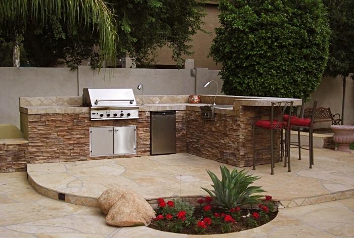 exemple de cuisine de jardin aménagée avec chaises de bar foncées à siège rouge, modèle d'ilot en pierres