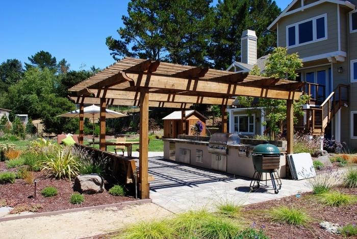 idée comment aménager une cuisine d'été dans le jardin avec toit de bois massif et modules en béton et inox