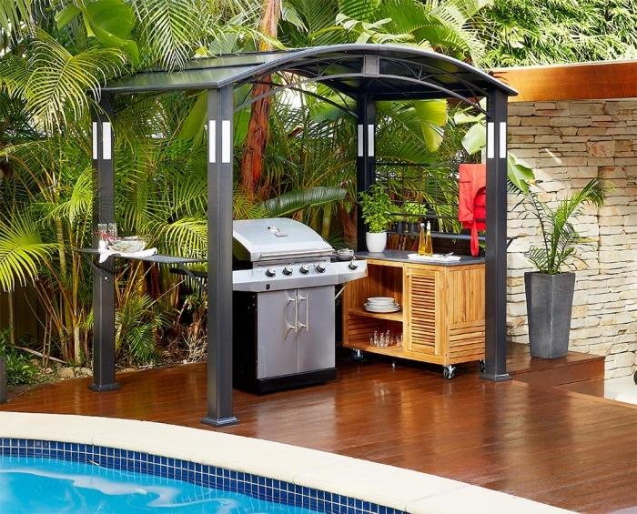 petite cuisine d'été avec toit et meuble de rangement en bois, modèle de barbecue inox avec armoires noir et gris