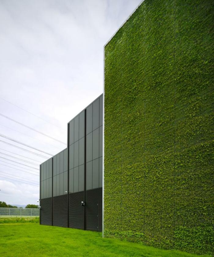 bâtiment industriel avec un mur vegetal exterieur, une partie de l'édifice est en métal noir et de fenêtres noires, grand champ vert
