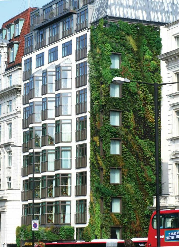 un grand mur végétalisé, édifice résidentiel avec un mur de la façade en vert et jaune, style d'édifice mi-classique et mi-moderne, partie du toit en verre transparent