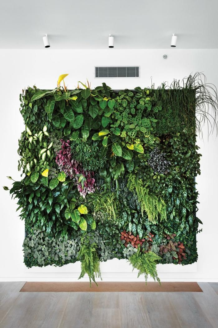 un salon moderne avec un mur végétal palette, en forme de grand carré avec des plantes multicolores en vert et rouge, trois spots lumineux en métal blanc pour illuminer le mur végétalisé