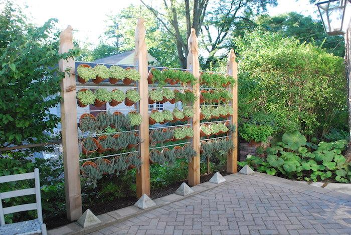 grande jardiniere brise vue sur pieds en bois avec pots suspendus pour cacher la vue du jardin