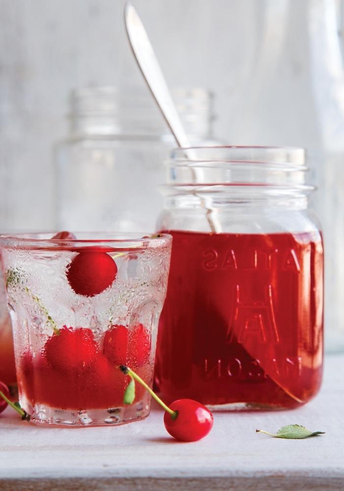idée limonade rouge aux cerises et eau froide servie dans un pot cocktail avec fruits et herbes fraîches