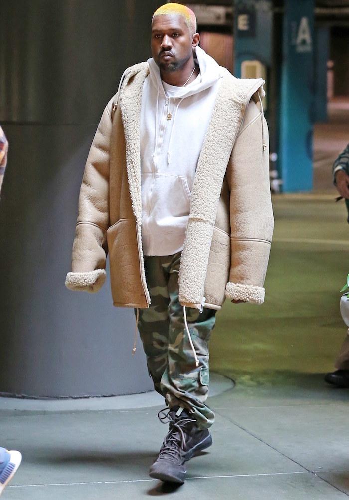kanye west avec cheveux courts colorés blond et orange et pantalon treillis