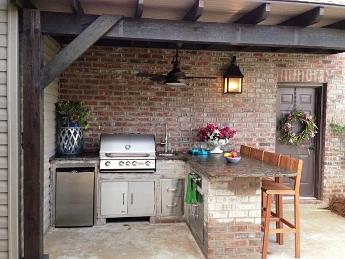 modèle d'abri cuisine extérieure avec toit en poutres de bois foncé et murs en briques rouges, cuisine en L extérieure