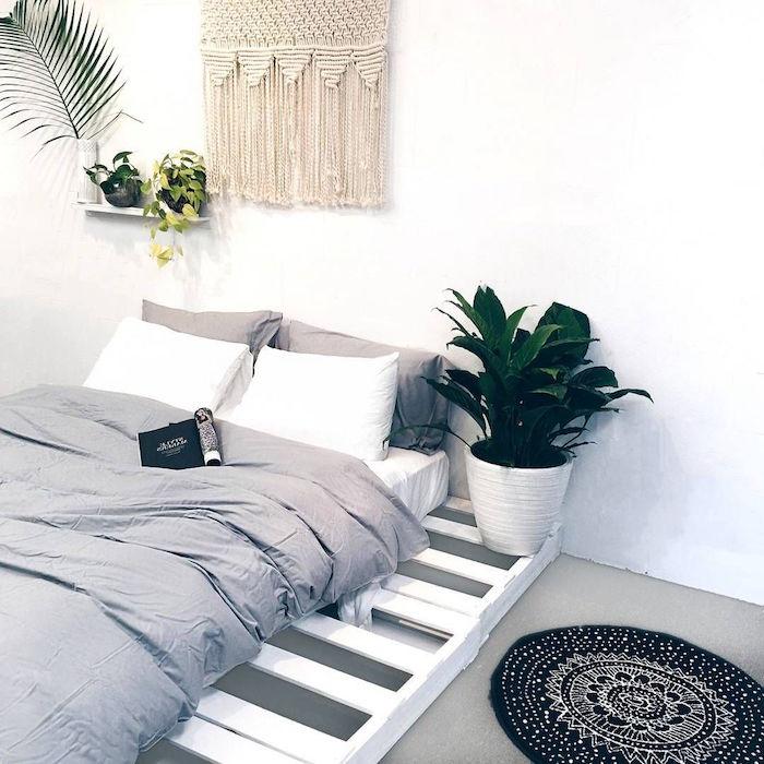 faire un lit en palette perdues blanches sur sol gris et murs blancs avec tissage mural en laine