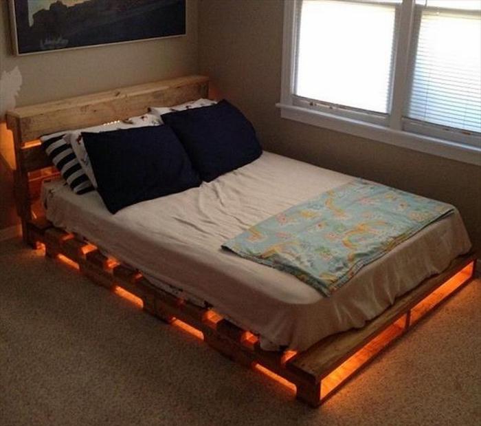 sommier en bois palette avec tete de lit et guirlande lumineuse sur moquette