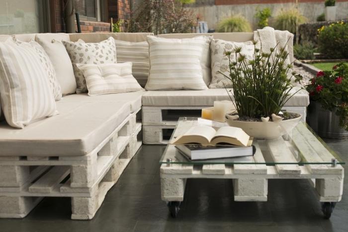 déco en couleurs neutres dans un coin extérieur aménagé avec un canapé d'angle en palettes et coussins décoratifs