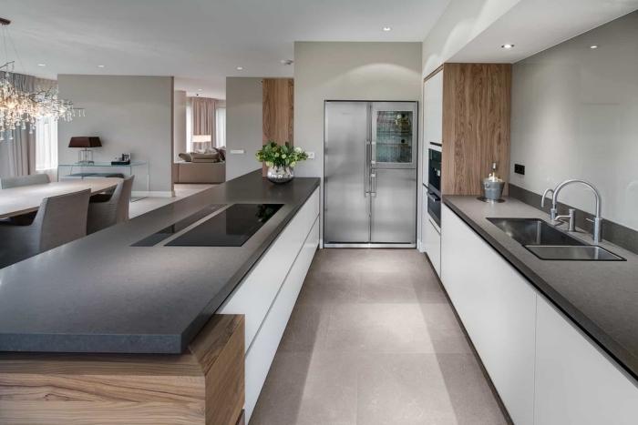 idée comment aménager une cuisine blanche et bois avec ilot central en comptoir gris foncé et armoires blanches sans poignées