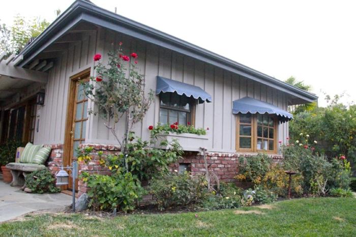 résidence de campagne, petite villa aux murs revêtus de bois peint en ivoire, store banne sur les fenêtres, couleur du tissu gris perle avec des ourlets ondulants blancs