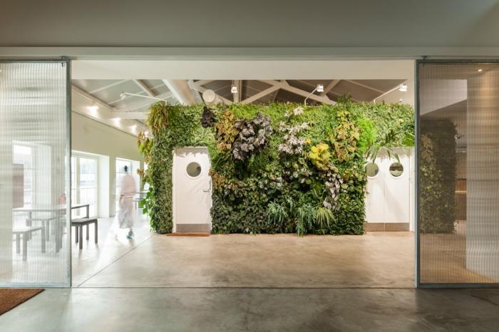 mur végétal intérieur, espaces ouverts dans un édifice SPA, plafond avec des poutres en bois, sol recouvert de revetement imitation marbre