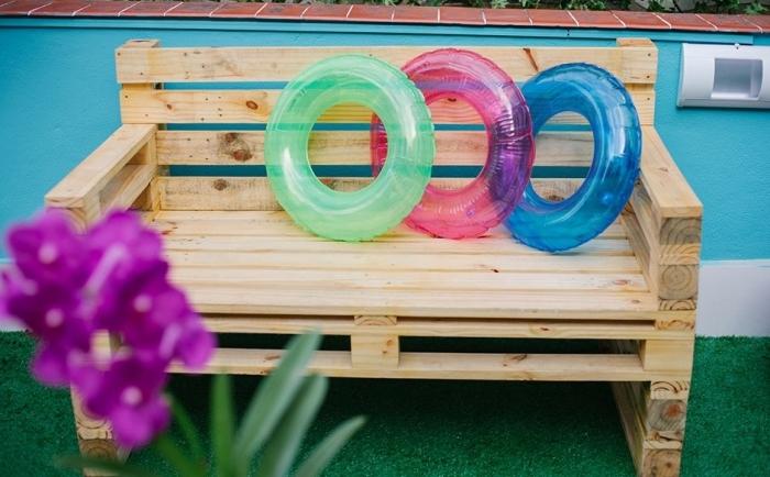 ambiance de style estival dans un coin de jardin aux murs bleus turquoise avec gazon artificiel et banquette en palette DIY