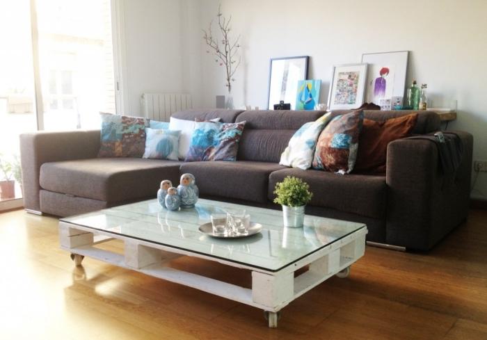 une table palette peinte en blanc avec un plateau en verre pour un rendu chic et moderne qui s'accorde avec l'ambiance du salon