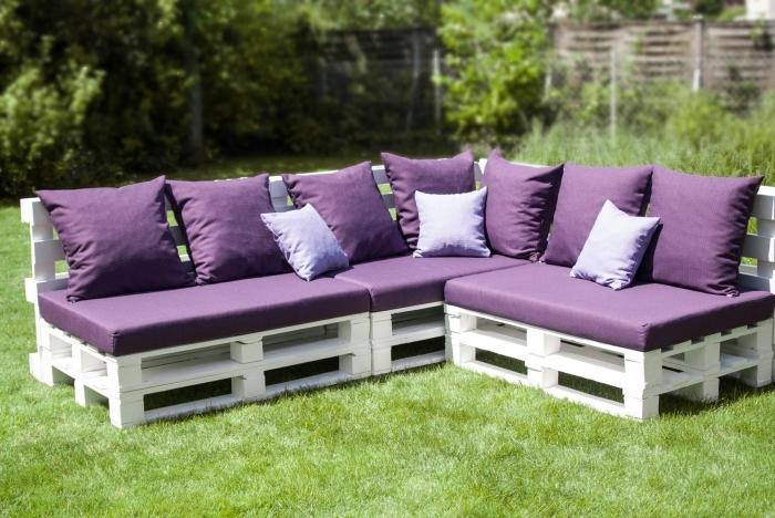 exemple de meuble DIY fabriqué en palettes de bois peint en blanc couvert de coussins et housses en violet