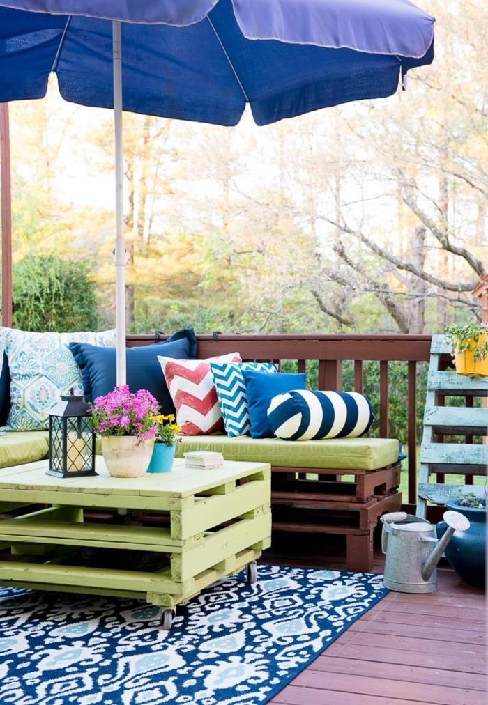 salon de jardin cosy fabriqué avec des palettes peintes en vert et marron, fabriquer une table basse originale avec deux palettes récupérées relookées avec de la peinture vert anis