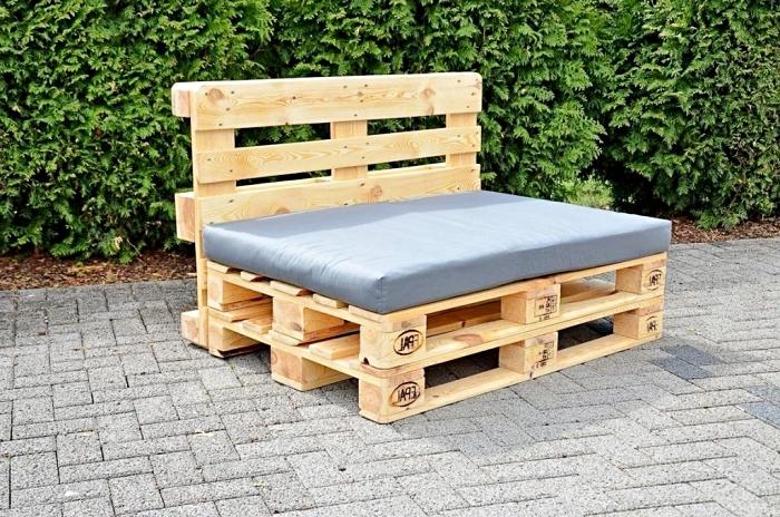 idée pour fabriquer meuble avec palettes, modèle de banc ou canapé en bois clair couvert de housse siège grise