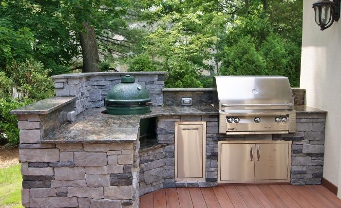 modele de cuisine aménagée sur une terrasse au parquet de bois marron avec ilot en pierres et barbecue en inox