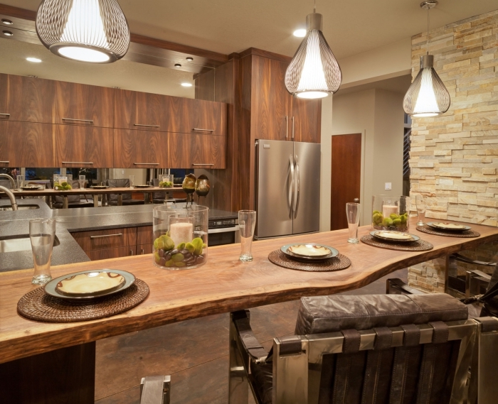 déco de cuisine avec ilot central en bois brut et meubles haut en bois foncé, modèle de cuisine au plafond blanc et mur en pierre