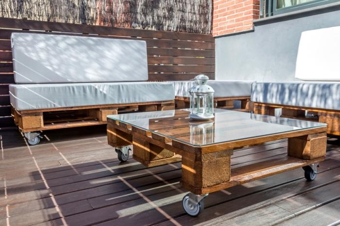 mini oasis dans le jardin avec meuble palette, modèle de banquette en bois foncé et table basse en bois et verre