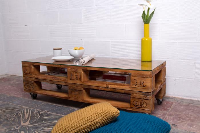 une table basse palette avec un plateau en verre et des roulettes pour un rendu design et moderne, rehaussé par un vase en céramique jaune moutarde