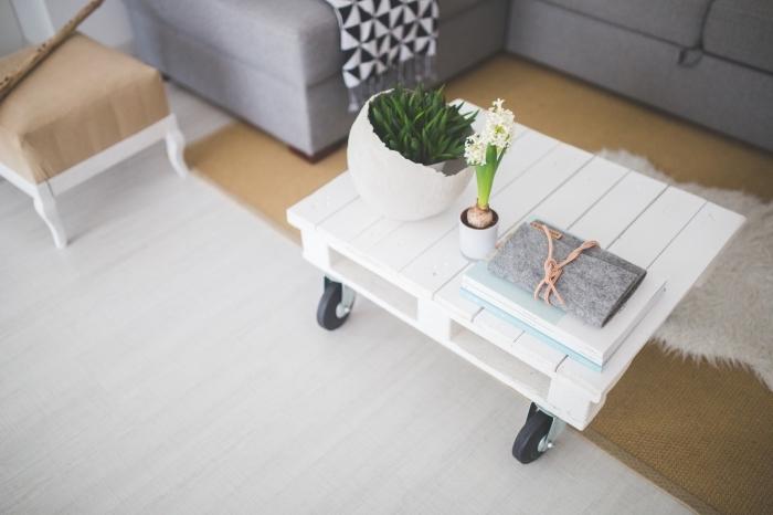 joli table basse palette blanche montée sur roulettes au look chic et aérien, décorée avec de simples plantes en cache-pots déco