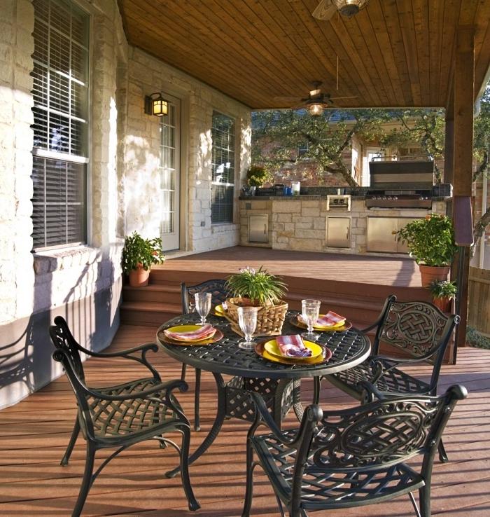 déco de terrasse avec table ronde et chaises en fer forgé, exemple evier exterieur sur coin cuisine en pierre et inox