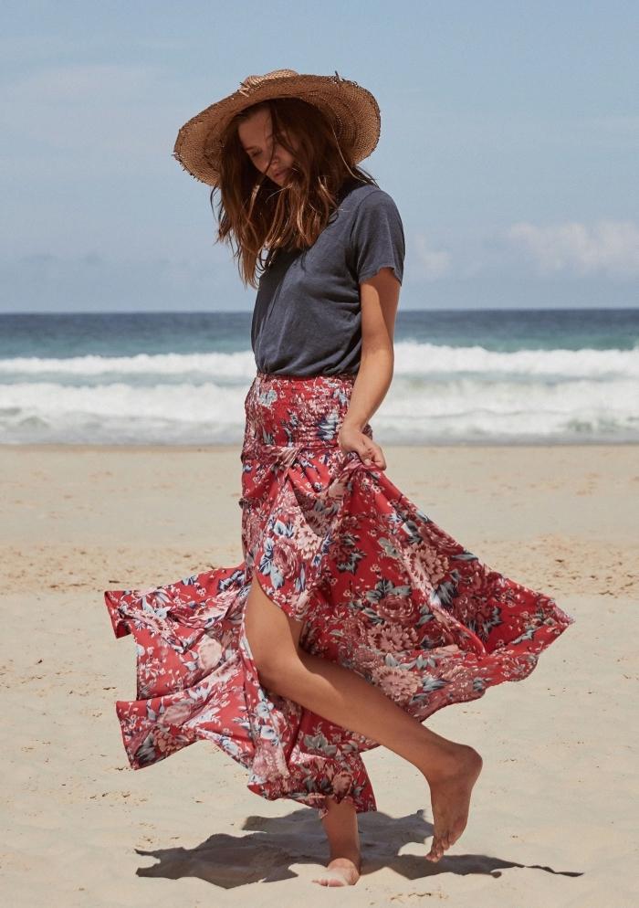 exemple de jupe fendue rouge aux motifs fleuris combinée avec t-shirt gris et capeline beige pour look boho chic de plage