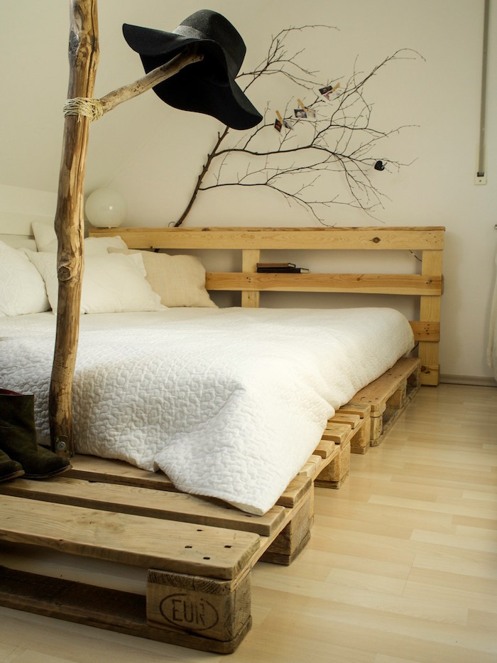 déco rustique avec lit sommier en palettes bas et branches d'arbre pour décoration nature