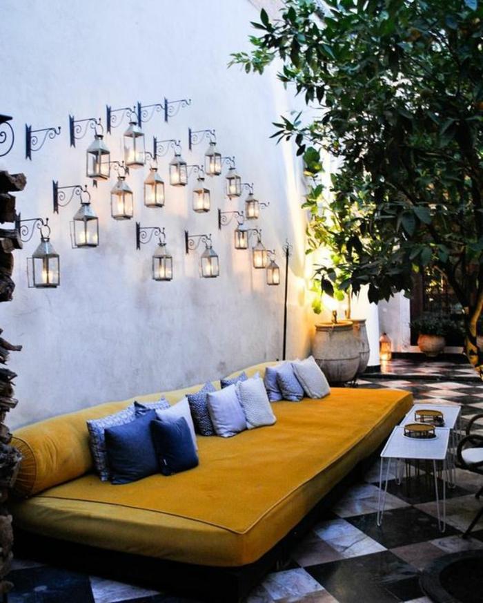 décorer un mur extérieur, aménagement extérieur maison, idee deco jardin exterieur, mur blanc avec une multitude de lanternes lumineuses, canapé grand et large en jaune et moutarde avec pleins de coussins bleus