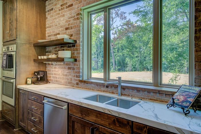 exemple de cuisine tendance 2018 avec mur en briques et meuble cuisine bas avec colonne en bois