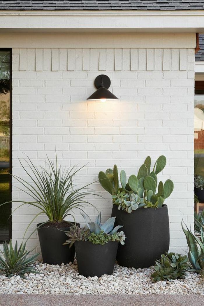 habillage mur exterieur, revetement mural exterieur, briques en couleur ivoire, lampe en métal noir en style industriel, trois porte-plantes taille grande avec des cactus et de l'aloe véra