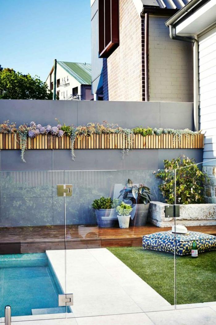 deco mur exterieur, habillage mur exterieur avec des porte-plantes en bois clair, clôture de jardin avec piscine en couleur gris pastel, herbe verte avec un gros coussin carré pour relaxer