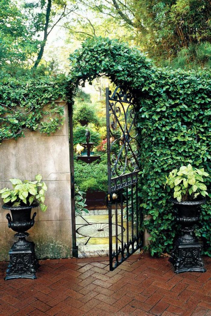 revetement mural exterieur, jardin classique en style vintage, habiller un mur extérieur avec des plantes rampantes vertes, grande porte en métal noir, deux vases noirs classiques avec des poignets des deux cotes