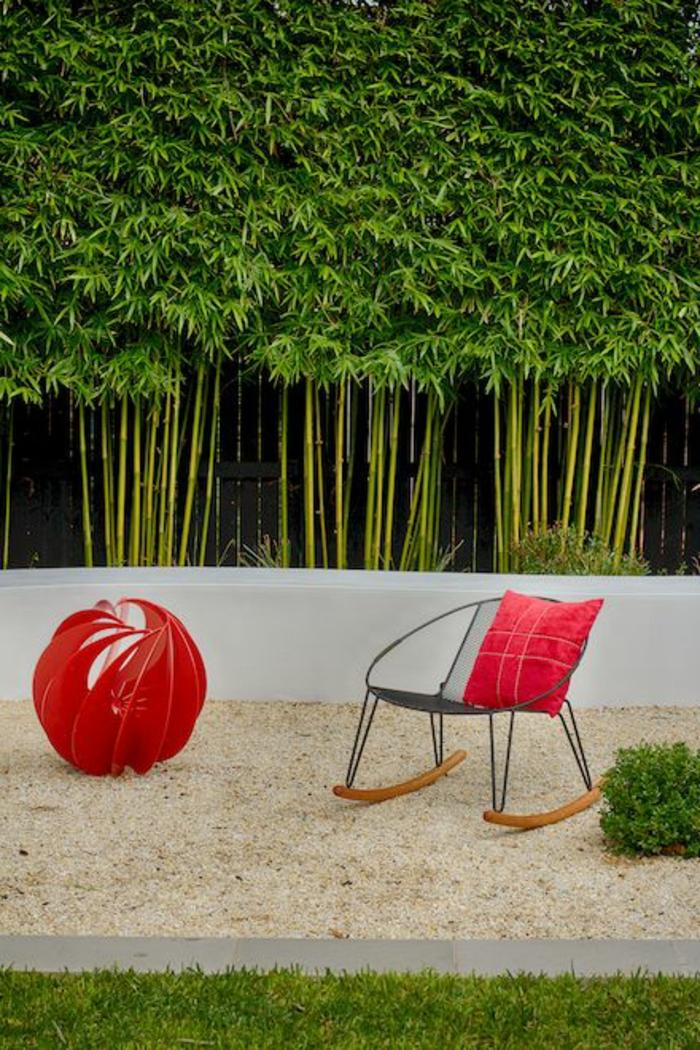 cloison végétale avec des tiges de bambou, coin de jardin relax avec un fauteuil en métal noir et bois clair, boule en tissu rouge, décoration design, sable fin, herbe verte bien entretenue, mur vegetal exterieur