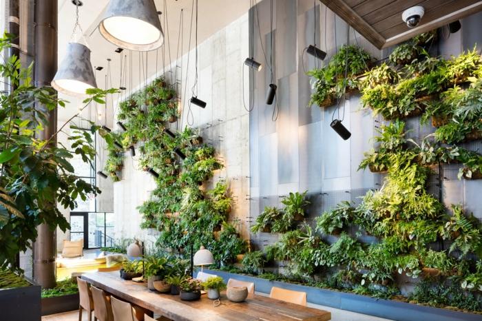 cuisine en style industriel avec un mur végétalisé interieur, luminaires en style industriel en métal couleur argent, murs recouverts de métal gris