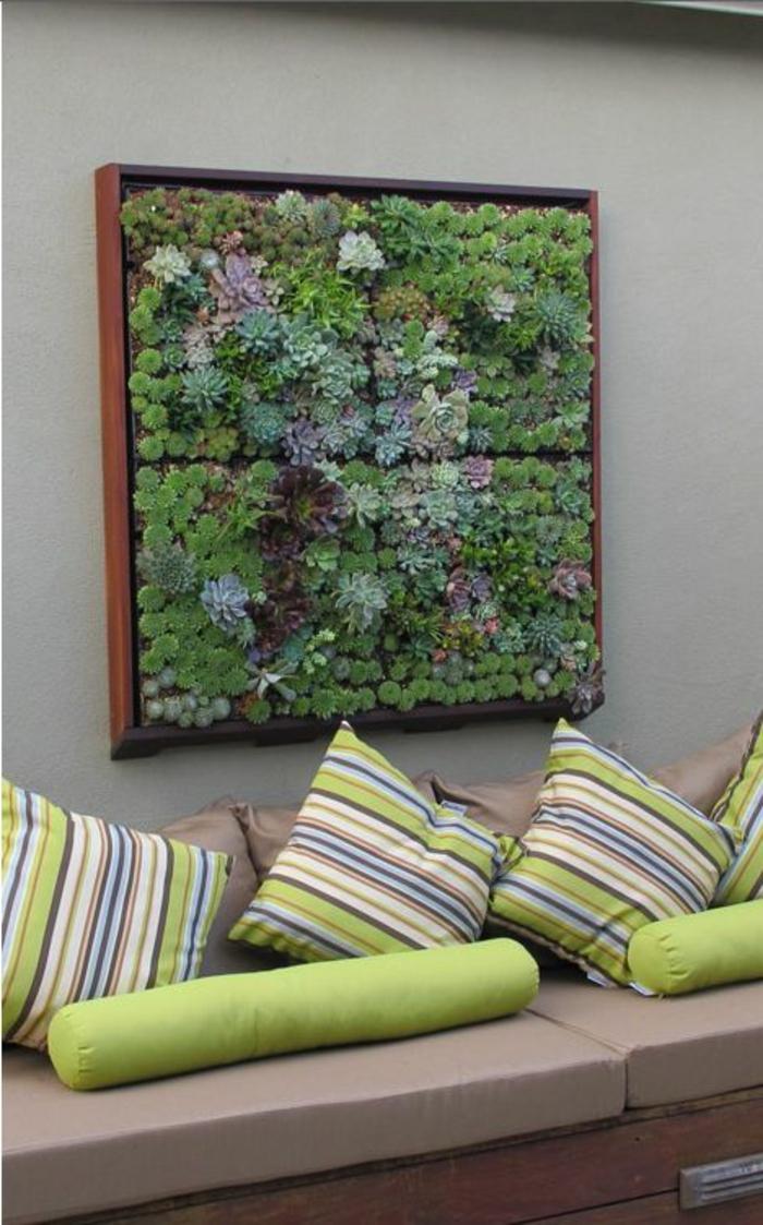 habillage mur exterieur, revetement mural exterieur avec vieux cadre de tableau, installé sur un mur vert menthe, cadre mur végétal rempli de plantes vertes, canapé en couleur taupe avec des coussins carrés aux rayures réséda et marron, coussins cylindriques en réséda