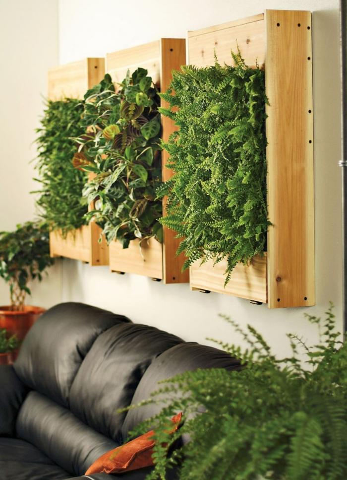 trois panneaux aux cadres en bois clair, mur végétal palette, mousse et plantes vertes basses, mur végétalisé interieur, salon avec canapé en simili cuir noir
