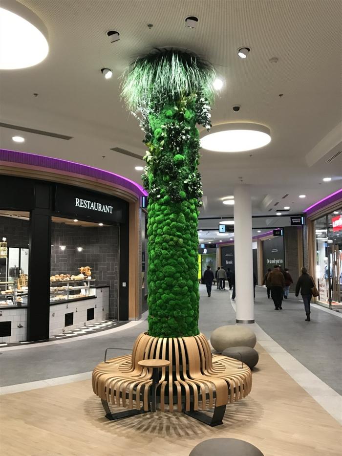 grand centre commercial, colonne décorative enveloppée de mousse verte et illuminée par six spots disposés en cercle autour de la colonne, culture verticale, mur végétalisé
