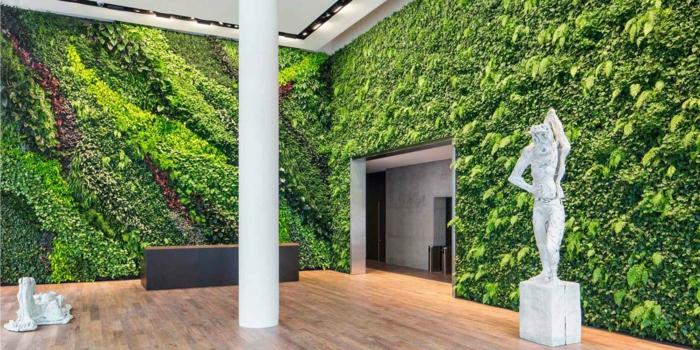 musée, salle d'expositions, murs avec des plantes vertes, mur végétalisé, statues blanches, figures de femmes, colonne blanche, plafond en noir et blanc illuminé discrètement