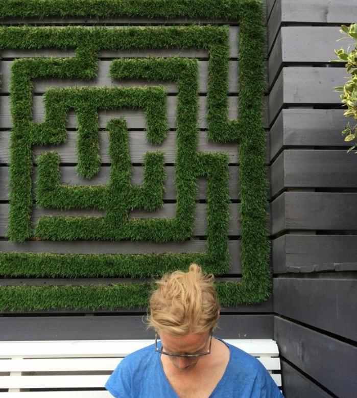 labyrinthe de mousse verte sur une cloison de jardin chic, mur vegetal exterieur au-dessus d'un banc blanc avec une femme qui lit