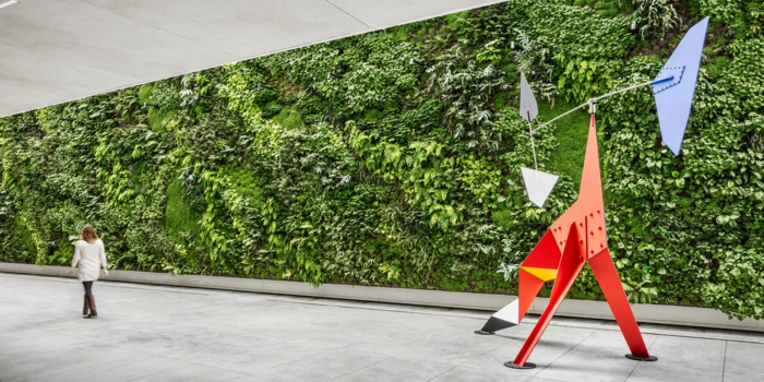 mur vegetal exterieur dans un espace d'expositions, mur végétalisé sur toute sa largeur, création figure en orange, noir et bleu pastel