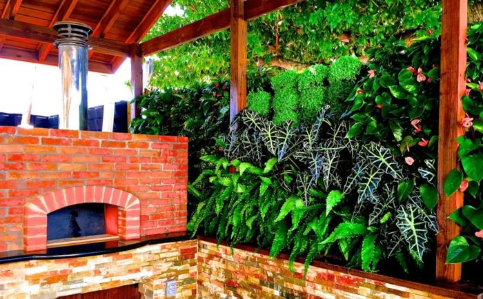 cloison végétale avec des plantes vertes et rouges, jardin avec cheminée en briques rouges, toit en bois rouge, dalles murales rouges et jaunes