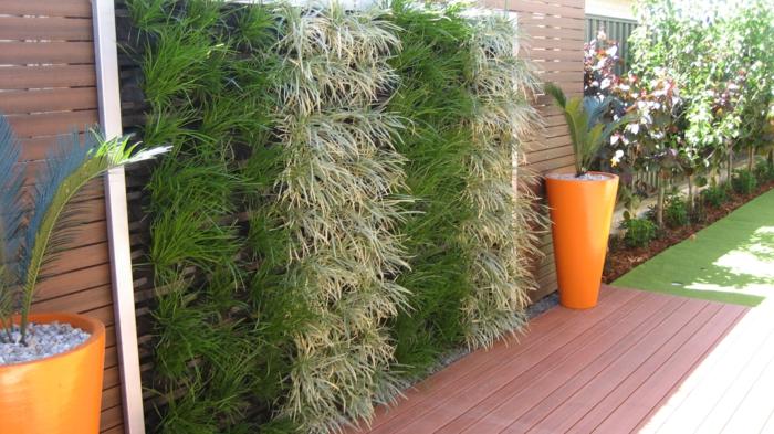 jardin vertical, panneaux colonnes avec des plantes vertes, deux cache-pots en forme conique en couleur orange avec des palmiers, mur végétalisé