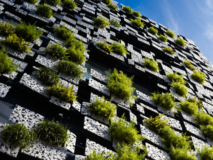 culture verticale, mur végétalisé, jardin vertical sur un édifice avec la façade en cubes de pierre, effets de labyrinthe, accents en vert, design futuristique